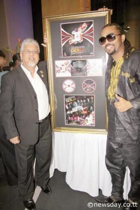 Planning Minister Dr Bhoe Tewarie (left) and soca superstar Machel Montano at the launch on Thursday evening of Government's collaboration with Montano on the music album 'Going For Gold' at the Central Bank Auditorium in Port-of-Spain. Author: ROGER JACOB © newsday.co.tt. All Rights Reserved.